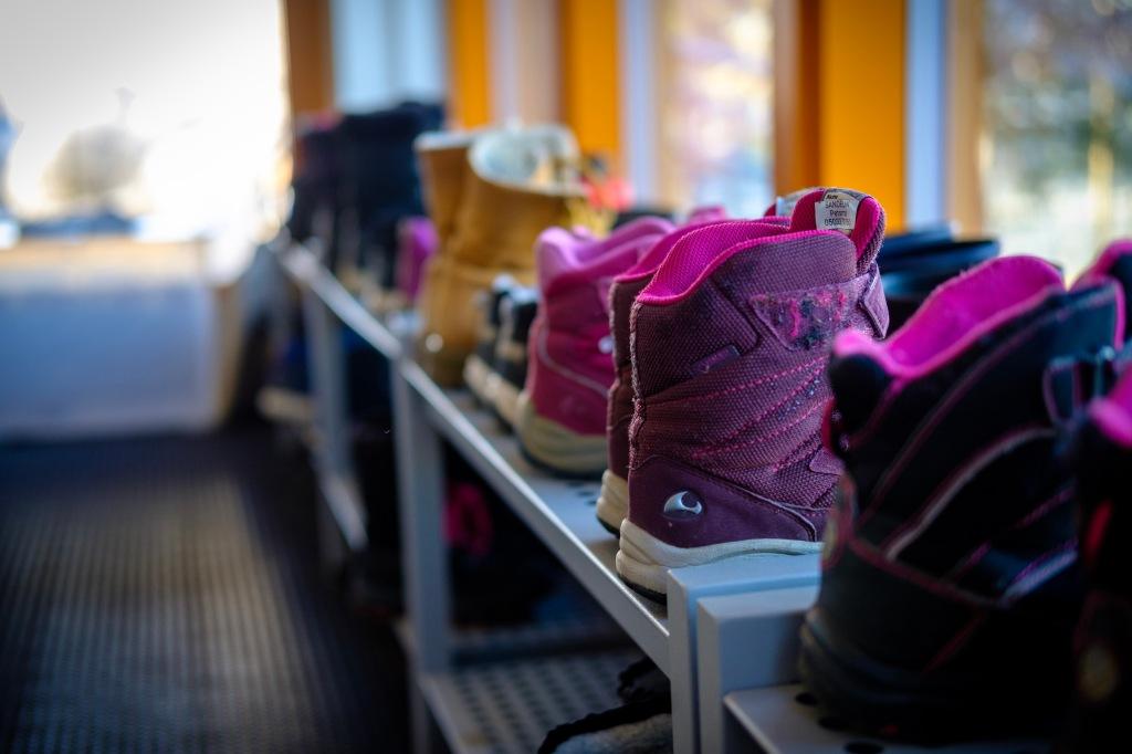 Bild av barnskor i snygga rader på en skohylla i en skola.