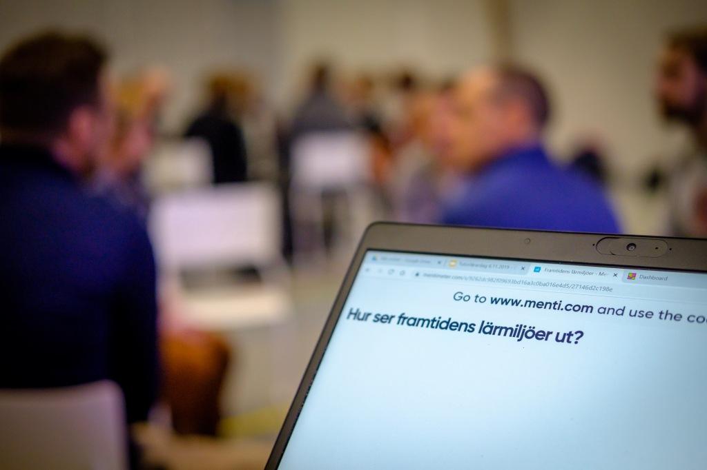 Bild av laptopskärm med frågan: Hur ser framtidens lärmiljöer ut? Personer syns suddigt i bakgrunden.